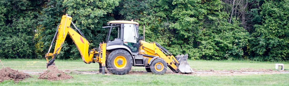 Affordable Septic Tank Systems - Bobcat digging ground surrounded by trees